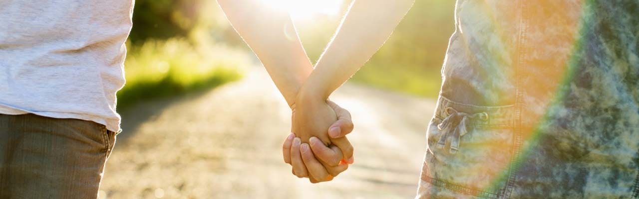 Closeup of two young people holding hands while walking outside in the sunshine