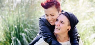 Young female couple smiling and hugging each other