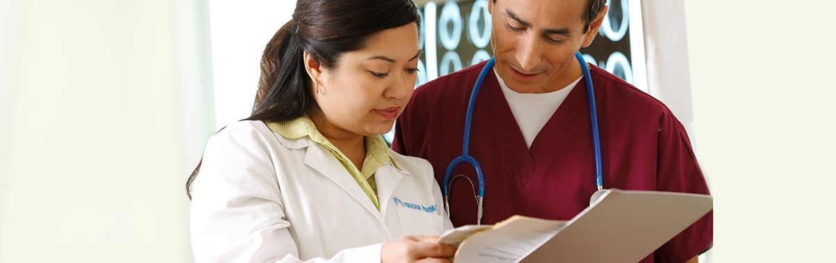 Two health care professionals review patient file