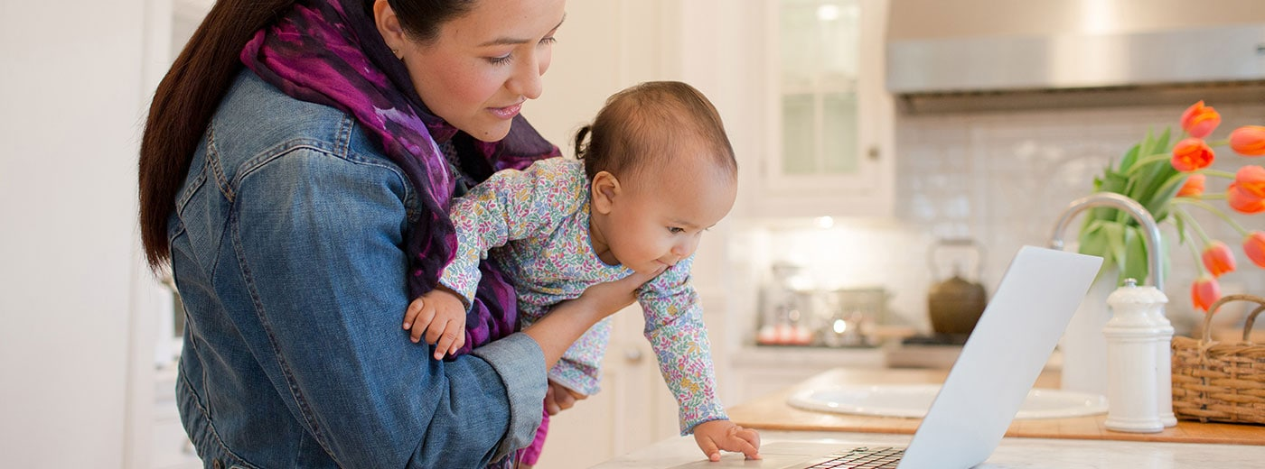 Mother holding baby looking at computer