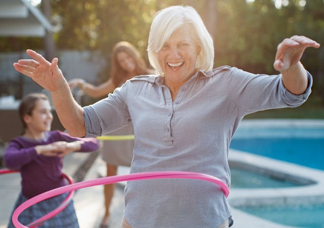 Photo of woman and children hula-hooping by pool
