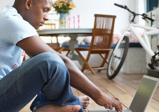 Photo of man sitting on floor using laptop