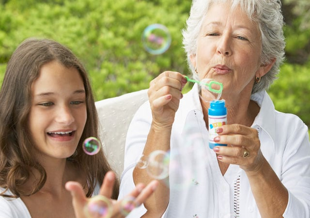 Photo of woman blowing bubbles with girl
