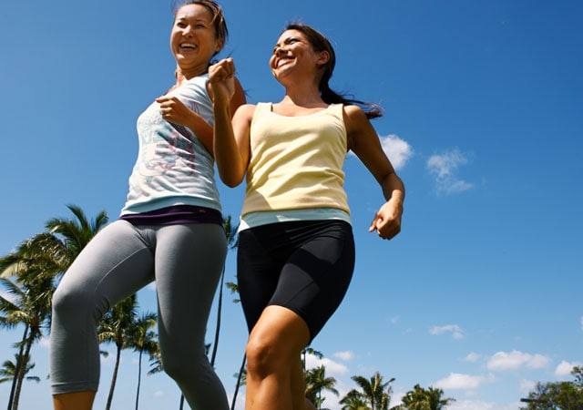 Photo of two women jogging near palm trees