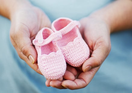 Hands holding pink baby shoes