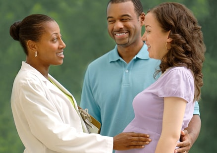 pregnant couple talking with female doctor