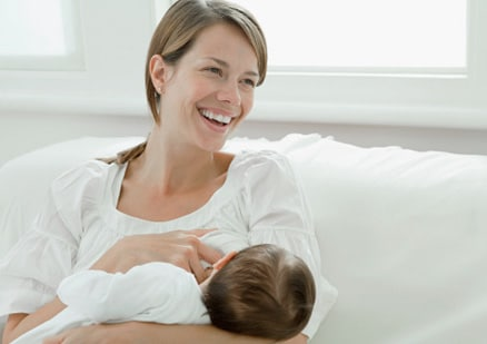 smiling woman breastfeeding