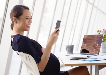 woman looking at cellphone in office