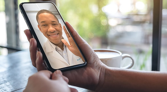 Doctor waving to a patient during a video visit