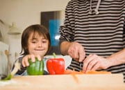 Child and parent chopping vegetables