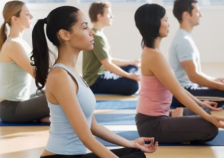 Group of young adults practicing yoga