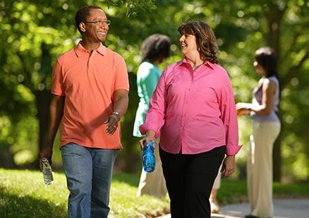 man and woman walking together and smiling