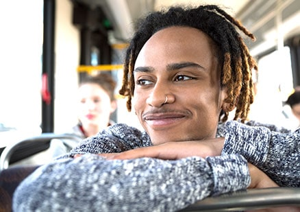 Man smiling and looking out of a bus window