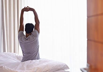 Man stretching in bedroom after waking up