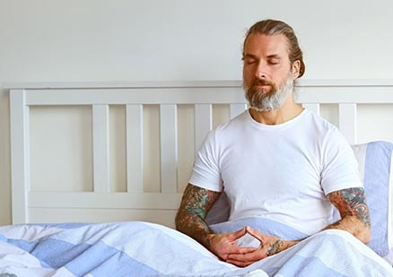 Man with tattoos meditating on bed