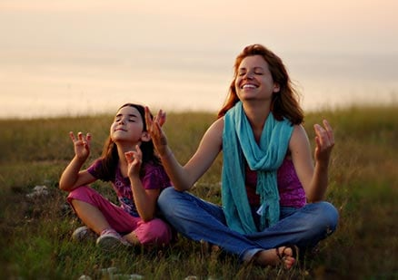 mother and daughter practicing meditation and smiling