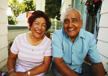 Older couple looking at the camera and laughing