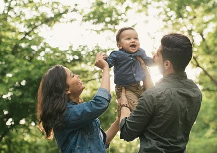 Parents smiling and playing with young baby outside