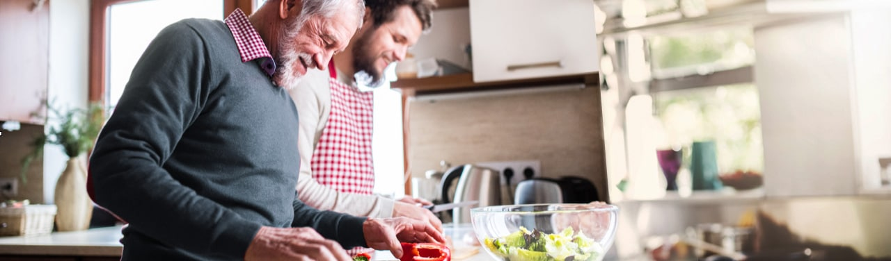 Smiling father and son focus on preparing salad in kitchen