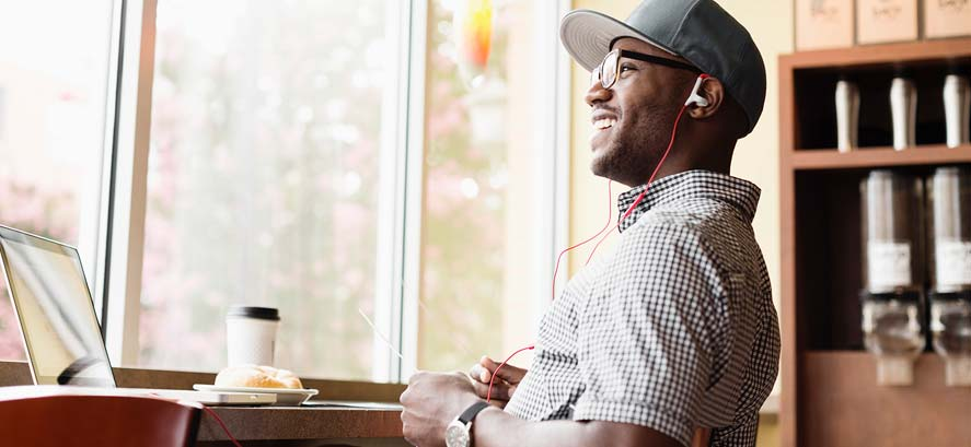 Smiling man with headphones and baseball cap