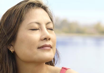 Woman looking peaceful with eyes closed outside