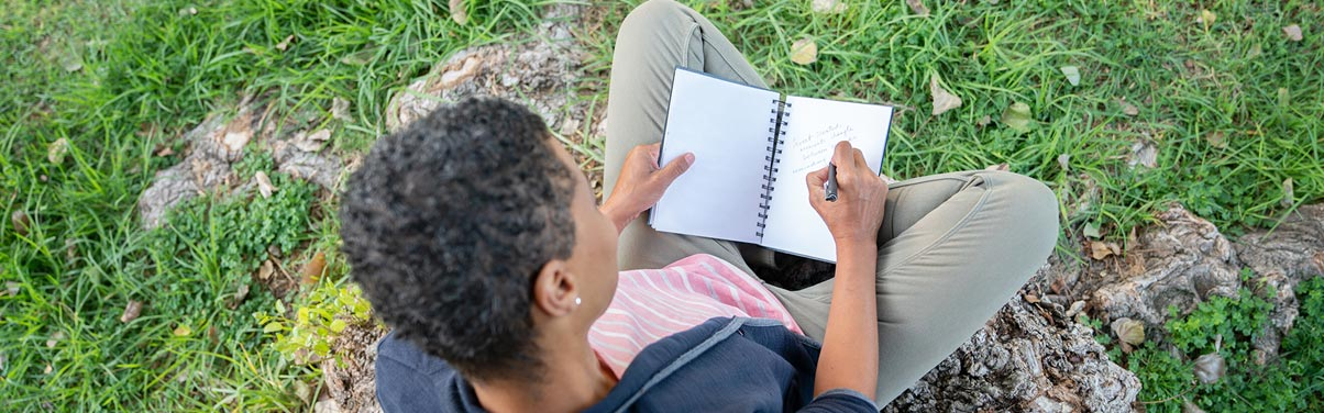 Woman sitting outside writing in journal