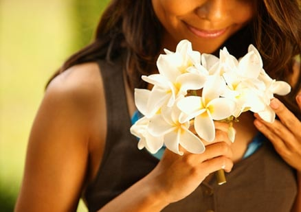 Woman smelling beautiful flowers and smiling