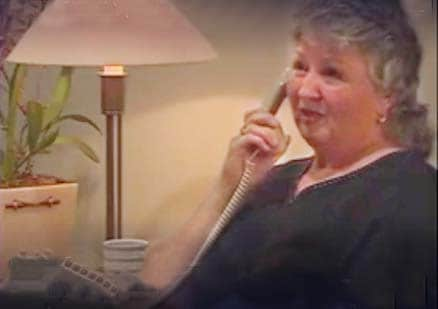 woman talks on phone at home