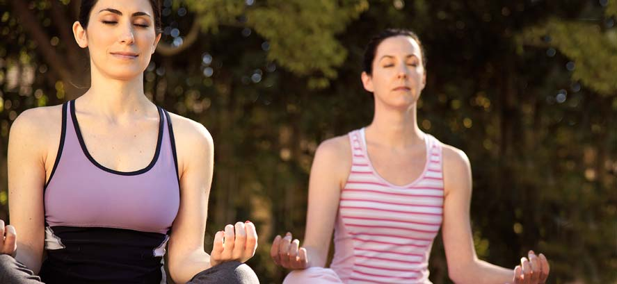 Women doing yoga and meditating outdoors