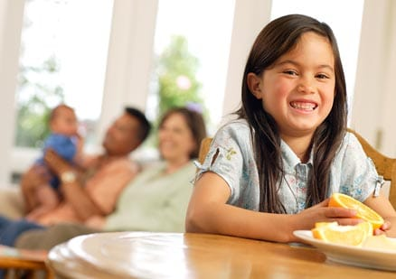 Young girl smiling at table with family in background