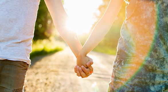 Closeup of two people holding hands while walking outside in the sunshine