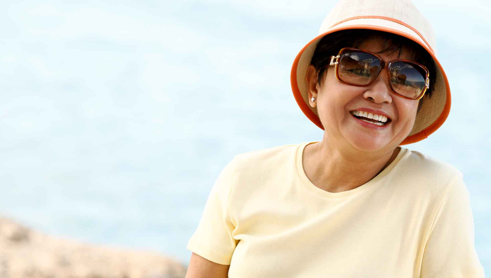 Photo of a woman in pink sun hat and sunglasses smiling