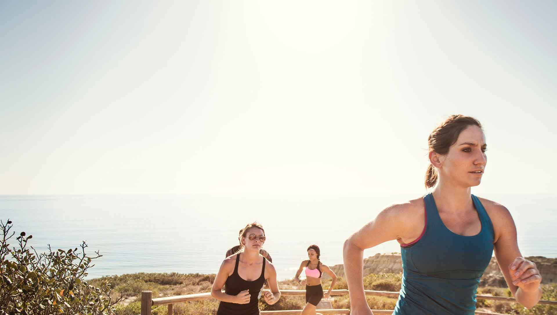 Photo of three women running on a hiking trail overlooking the ocean