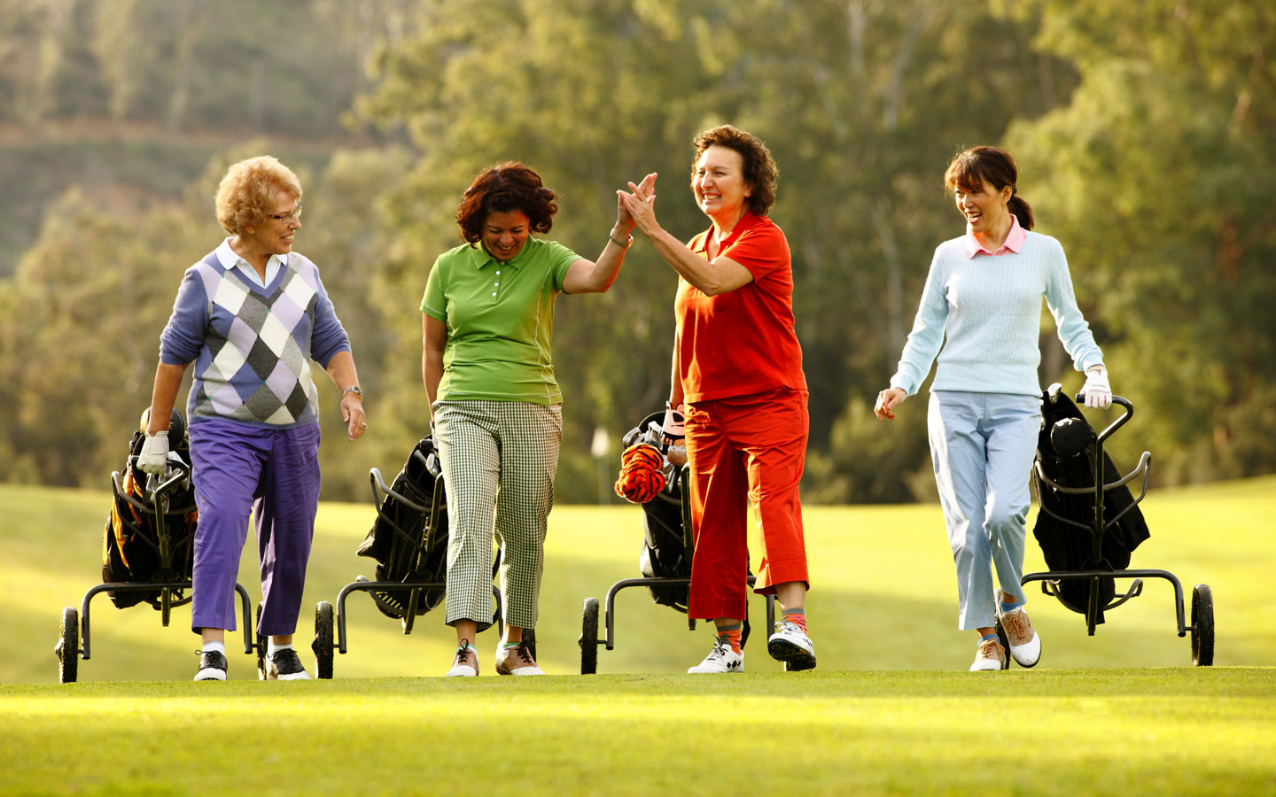 Four women walking on a golf course