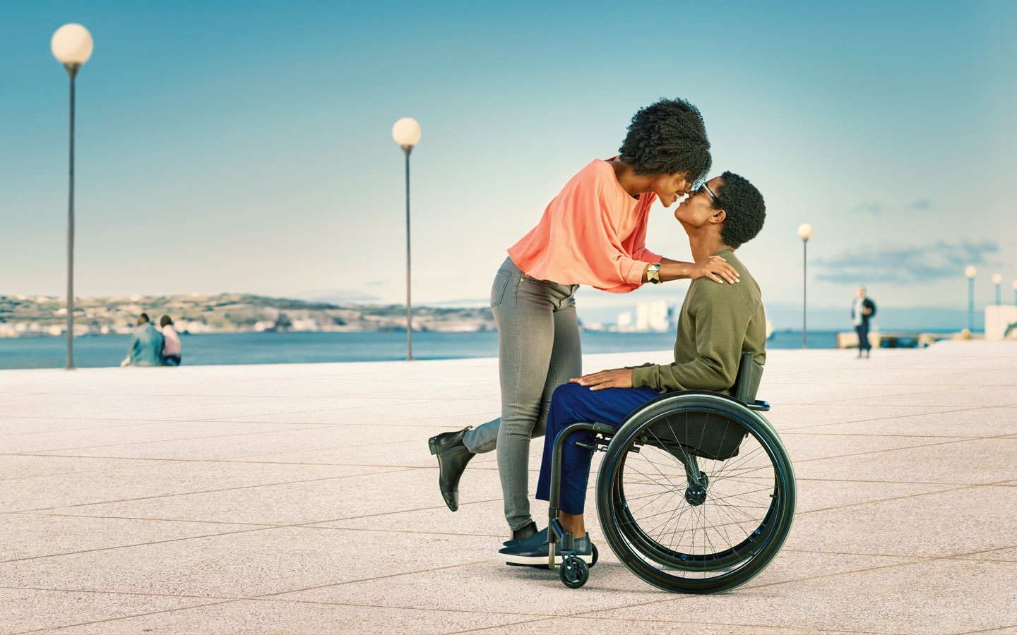 Couple sharing a moment with man in wheelchair